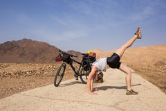 Young woman relaxing yoga during bicycling trip. Happy traveller relax during trip in Israel desert Royalty Free Stock Photos