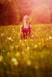 Young woman in a relaxing yoga pose at the evening meadow Royalty Free Stock Images