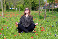 Young woman relaxing in yoga pose in meadow Royalty Free Stock Photos