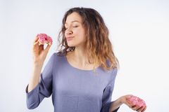 Young woman with relish eating a donut. The concept of harmful nutrition.  Stock Photo