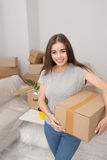 Young woman relocating, holding box ready to unpack things in newly rented apartment. Stock Photography