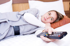Young woman with a remote control Stock Images