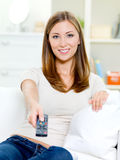 Young woman with remote control sitting. Happy young woman with remote control sitting on the sofa and watching TV Royalty Free Stock Photos