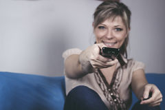 Young woman with remote control sitting on sofa close-up focused on remote control. Stock Image