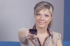 Young woman with remote control sitting on sofa close-up focused on remote control. Stock Photos
