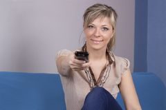 Young woman with remote control sitting on sofa close-up focused on remote control. Royalty Free Stock Photography