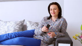 Young woman with remote control watching television stock footage
