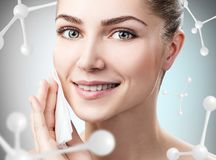 Young woman remove makeup among molecules Royalty Free Stock Image