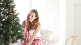 A young woman removes gifts and decorations for the Christmas tree stock footage