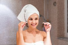 Young woman removes under-eye patches looking in mirror at home in bathroom. Beauty skincare and wellness morning concept.  royalty free stock image