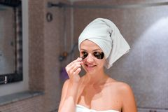 Young woman removes under-eye patches looking in mirror at home in bathroom. Beauty skincare and wellness morning concept.  stock photos