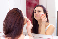 Young woman removing makeup in bathroom Stock Photo