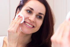 Young woman removing makeup in bathroom Stock Photos