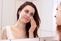 Young woman removing makeup in bathroom Stock Photography