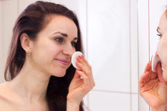 Young woman removing makeup in bathroom Royalty Free Stock Image