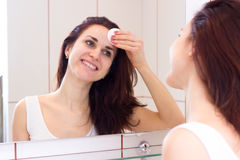 Young woman removing makeup in bathroom Royalty Free Stock Photography