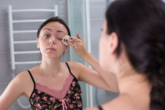 Young woman removing makeup from eyes in the bathroom Royalty Free Stock Photos