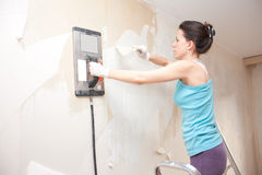 Young woman removing wallpaper Stock Photography