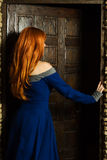 Young woman in renaissance dress open door Royalty Free Stock Images