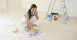 Young woman renovating or decorating her new home. Sitting on the floor looking at a collection of color swatches from a paint shop Stock Photography