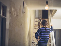 Young woman renovating a staircase. A young woman is standing by a staircase she is renovating Stock Images