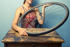 Young woman repairing bicycle wheel Stock Images