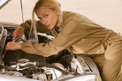Young woman repairing car royalty free stock photography