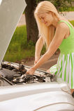 Young woman repairing car Stock Photos