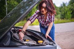 Young woman repairing her car Royalty Free Stock Images