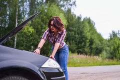 Young woman repairing her car Royalty Free Stock Photo
