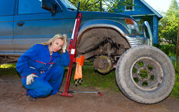 The young woman repairs the car Stock Photography