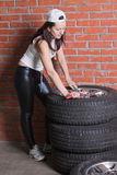 Young woman repairs wheel. Beautiful young woman repairs wheel Royalty Free Stock Photo