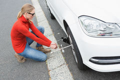 Young woman replacing tire Stock Image