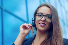 Young woman representative talking in a phone microphone for customer support royalty free stock image