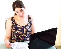 Young woman resigned to bill paying. A pretty  young  woman paying her bills on line using a laptop computer appears stressed Royalty Free Stock Images