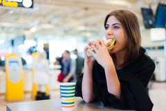 Young woman at a restaurant in international airport Stock Photos