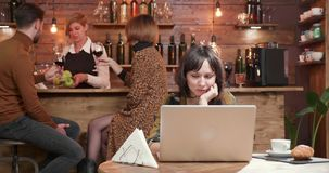 Young woman in a restaurant reading a text on her laptop stock video