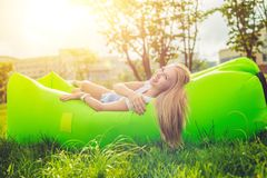 Young woman resting on an air sofa in the park. Lamzac Royalty Free Stock Photography