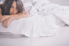 Young woman resting as she lies awake in bed. Woman resting on bedroom royalty free stock photos