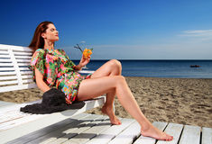 Young woman resting on the beach. Woman sunbathing and enjoying a cocktail at the beach stock photos