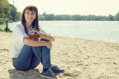 Young woman resting at the beach with old camera. Young smiling woman resting at the beach with old camera. Hipster girl posing near water. Warm color toned Stock Image