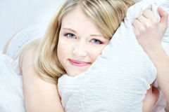 Young woman resting in the bed. Smiling young woman resting in the bed royalty free stock photos