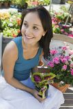 Young woman resting on bench in garden centre Stock Photo