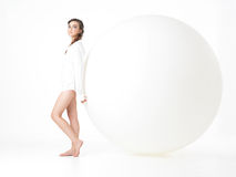 Young woman resting on big, white balloon Stock Photos