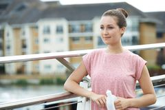 Young Woman Resting On City Bridge During Exercise Stock Photo