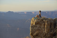 Young woman resting on cliff after hiking, Grand Canyon. Young Chinese woman sitting on cliff, Grand Canyon Stock Photo
