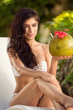 Young woman resting with coconut in hands stock photo