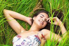 Young woman resting and day lying down on green grass Stock Photo