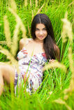 Young woman resting and day lying down on green grass Royalty Free Stock Photography