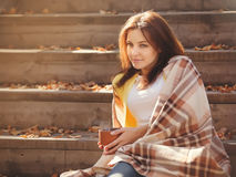 Young woman resting and drinking tea sitting in autumn garden on the steps, wrapped in a woolen plaid blanket. Royalty Free Stock Photo
